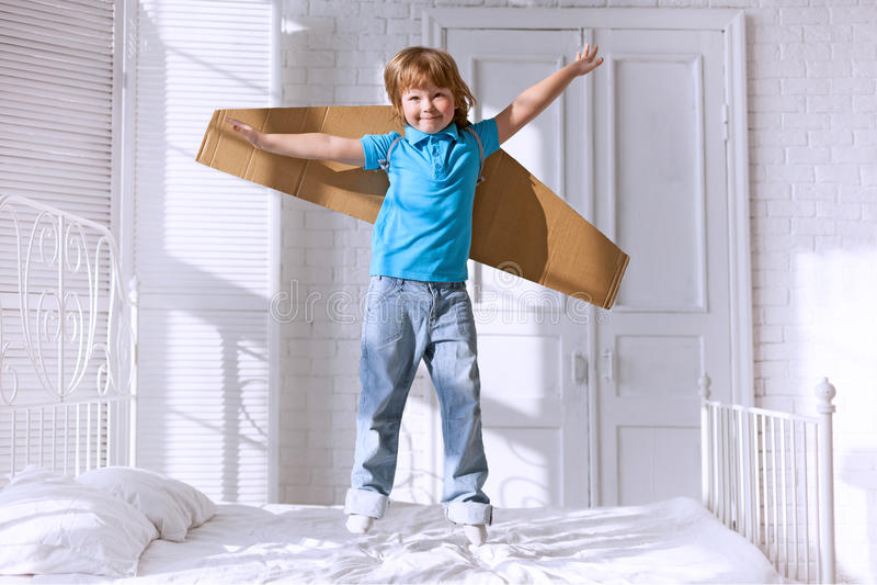 Dziecko z kartonem uskrzydla doskakiwanie na łóżku zdjęcie stock