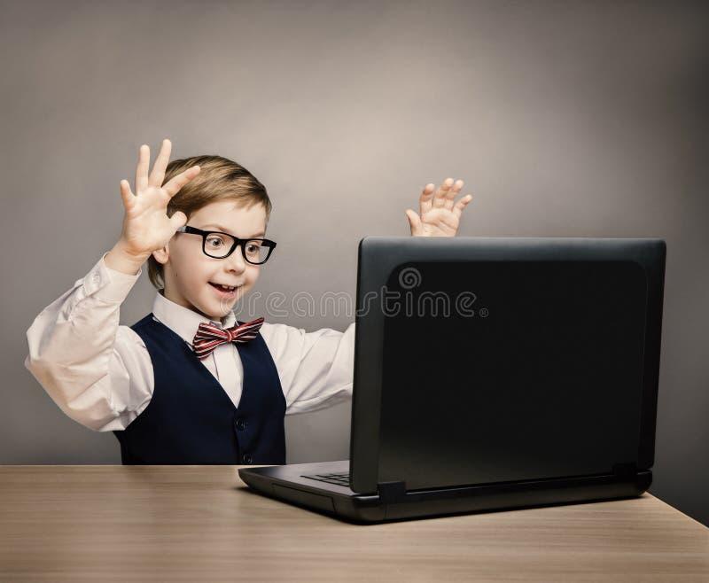 Dziecko Z laptopem, Little Boy w szkłach Zadziwiał Przyglądającego komputer zdjęcia stock