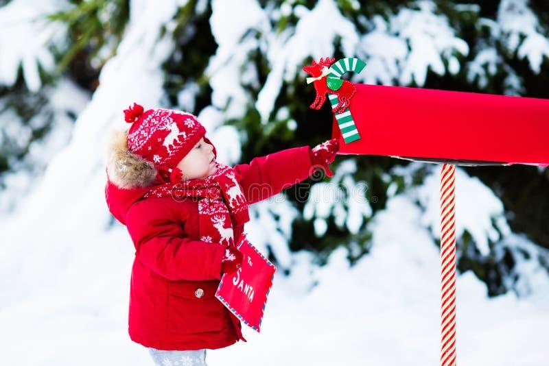 Dziecko z listem Santa przy Bożenarodzeniową skrzynką pocztowa w śniegu obrazy royalty free