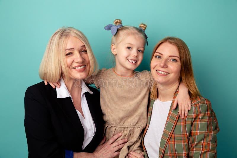 Dziecko z matką i babcią wpólnie uściśnięcie i ono uśmiecha się odizolowywający fotografia royalty free