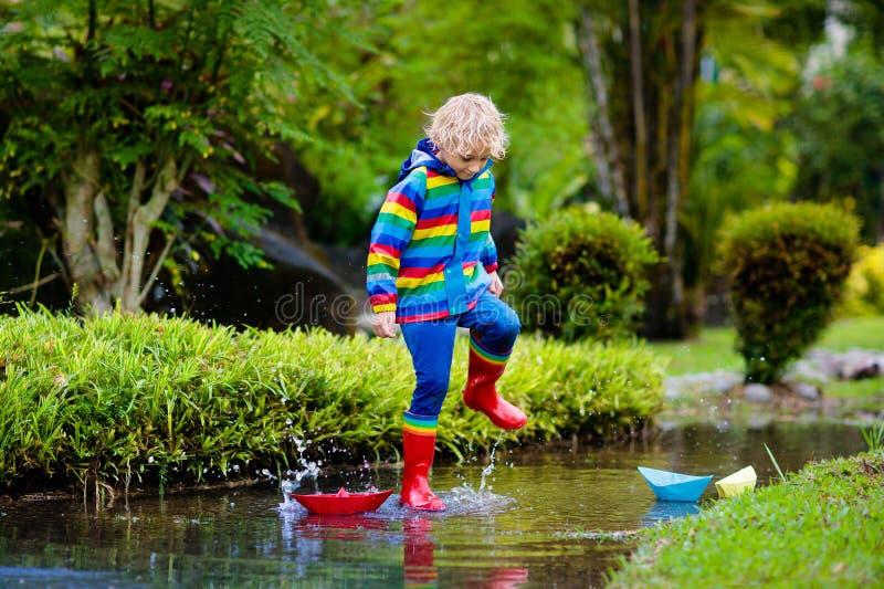 Dziecko z papierową łodzią w kałuży Dzieciaki deszczem obraz stock