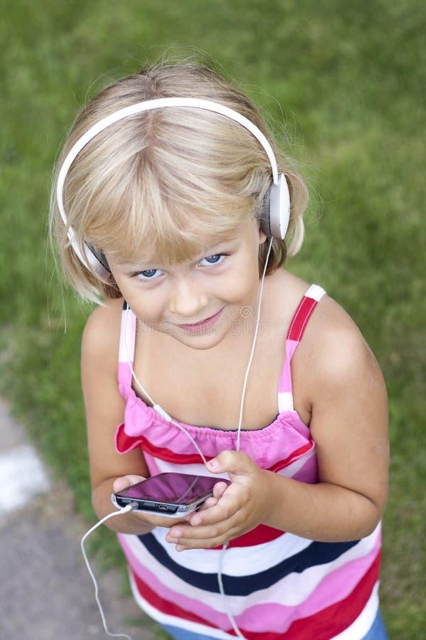 Dziecko z smartphone i hełmofonami fotografia royalty free