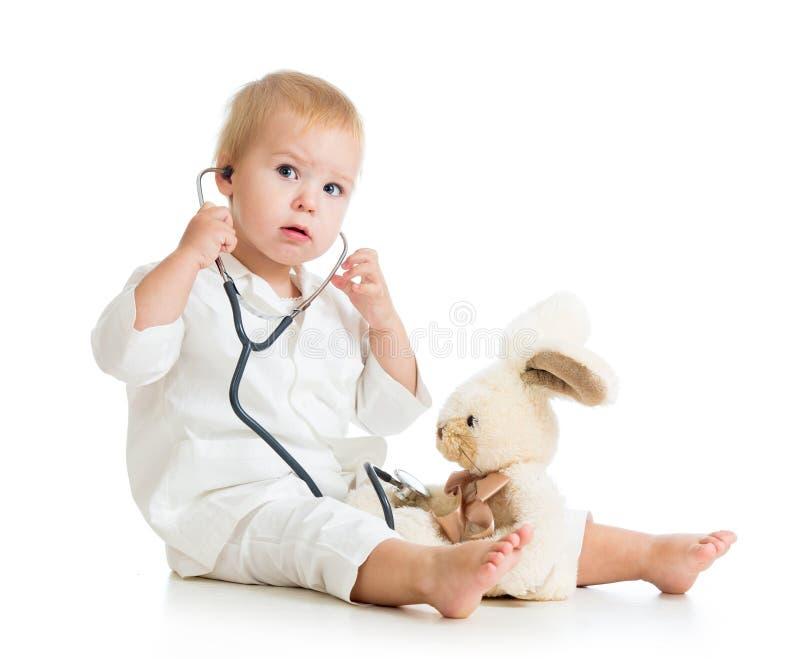 Dziecko z ubraniami doktorska egzamininuje zając zabawka zdjęcie stock