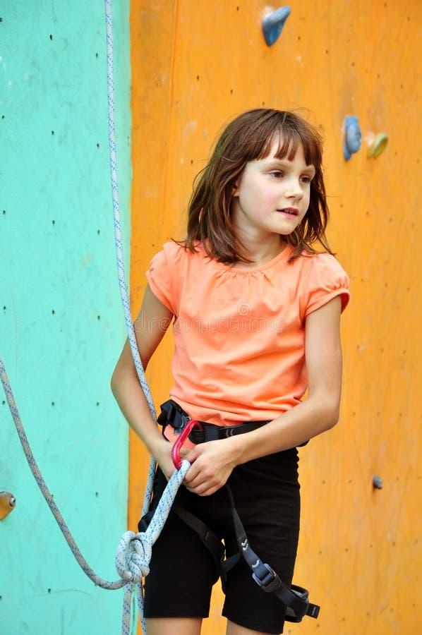 Dziecko z wspinaczkowym wyposażeniem przeciw stażowej ścianie fotografia stock