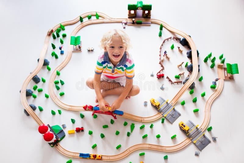 Dziecko z zabawka pociągiem Żartuje drewnianą kolej zdjęcie stock