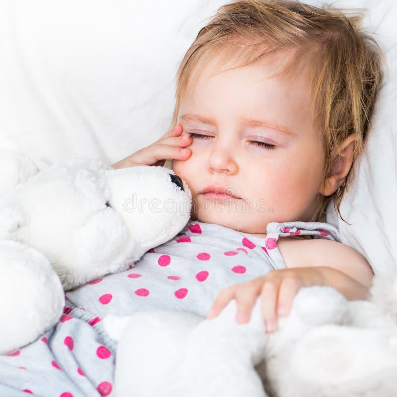 Dziecko z zabawki w białym łóżku zdjęcie stock