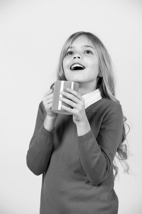 Dziecko z zdziwionego twarz chwyta błękitną filiżanką na pomarańczowym tle fotografia stock