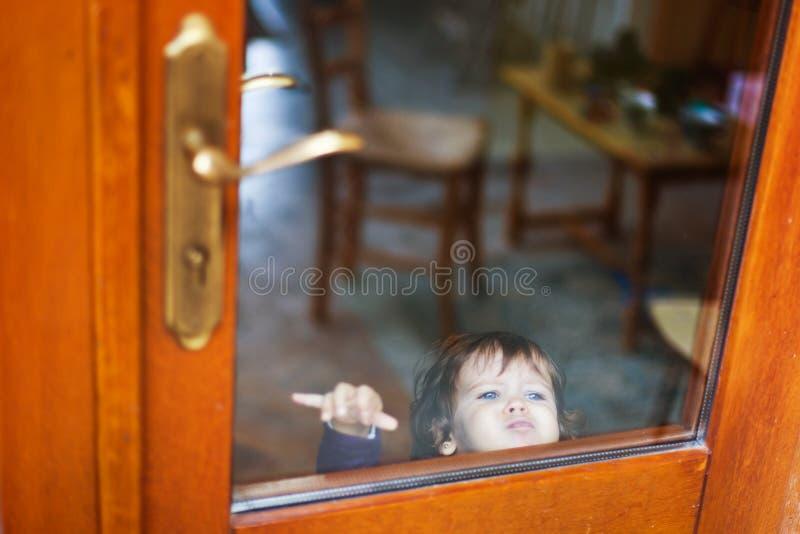 Dziecko za zamkniętym drzwi fotografia stock