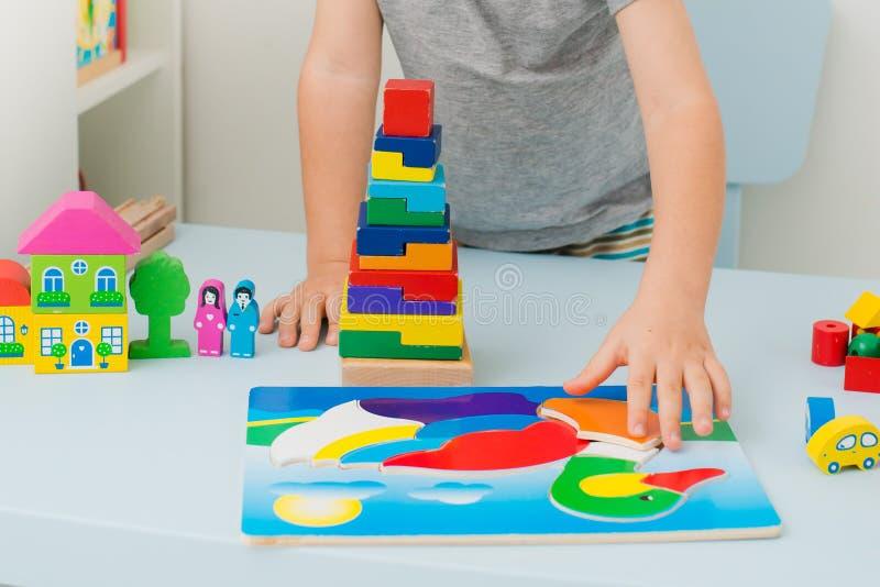 Dziecko zbiera drewnianej kaczki rozwija łamigłówkę przy stołem Zakończenie ręka z zabawką obrazy stock