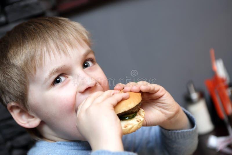 Dziecko zjadliwy hamburger fotografia stock