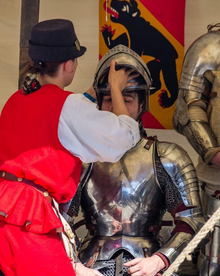 Dziedzic pomaga rycerzowi zdjąć kask po bitwie fotografia royalty free