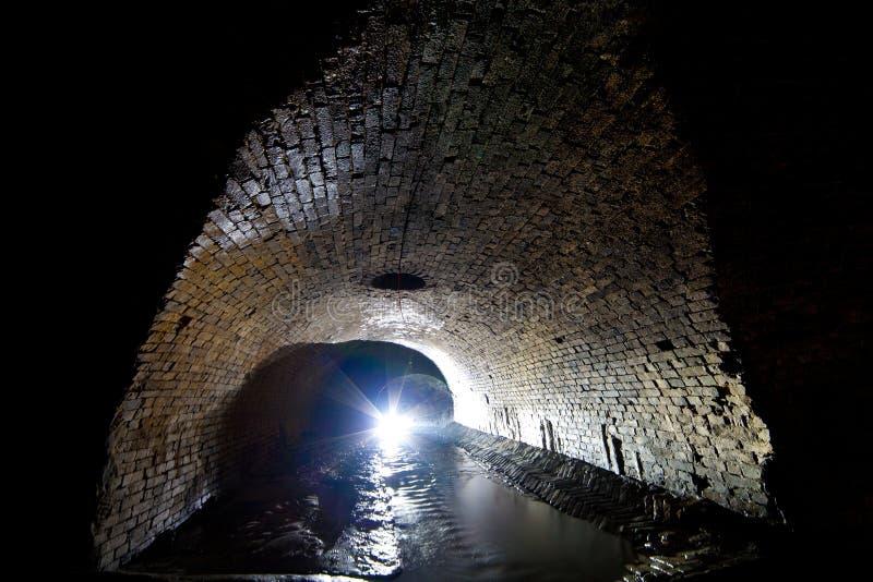 Dziejowa rzeka w starym ceglanym podziemnym poborcy zdjęcie stock