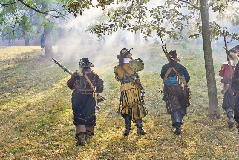 Dziejowy reenactment dzień Brno Aktorzy w dziejowych piechota kostiumach atakują z muszkietami Słońce błyszczy przez armatniego p obraz stock