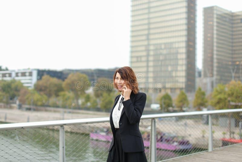 dziennikarz kobieta w biznesie odziewa opowiadać na smartphone zdjęcia stock