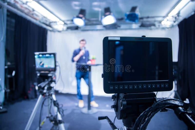 Dziennikarz w telewizyjnym studiu opowiada w mikrofon, rozmyte ekranowe kamery obrazy royalty free
