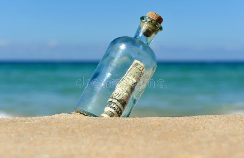 Dziesięć dolarów rachunku w butelce na plaży obrazy royalty free