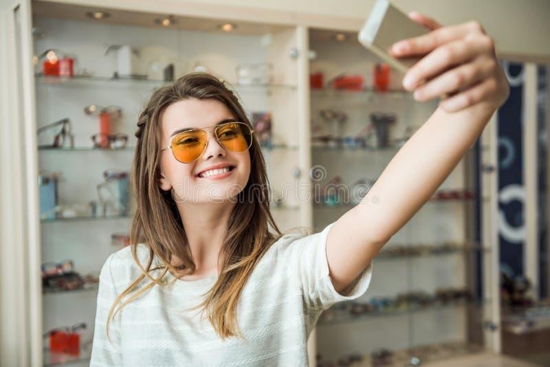 Dziewczyn życia nigdy stwarzają ognisko domowe bez smartphone, Elegancka europejska brunetka próbuje na okularach przeciwsłoneczn zdjęcia stock