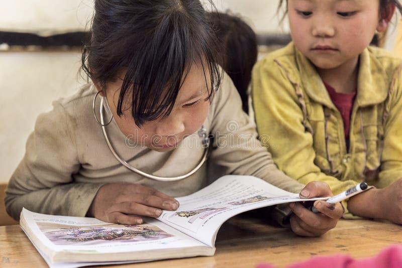 Dziewczyn czytelnicze książki wśrodku sala lekcyjnej w małej wiosce, Sapa, Wietnam zdjęcie stock