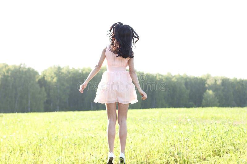 Dziewczyn menchii suknia jest skokowym łąkowym latem, szczęścia pojęcia zabawa pomysł, relaks postaci słońca radość obraz royalty free
