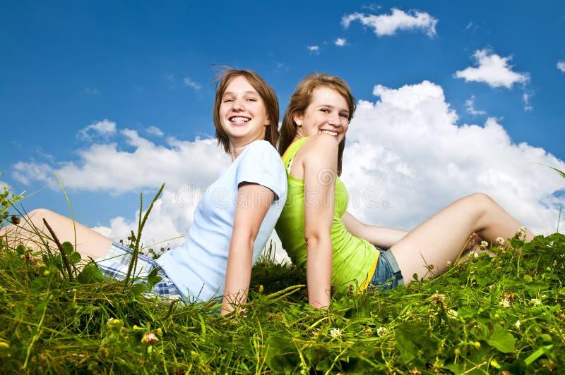 dziewczyn potomstwa łąkowi siedzący obrazy stock