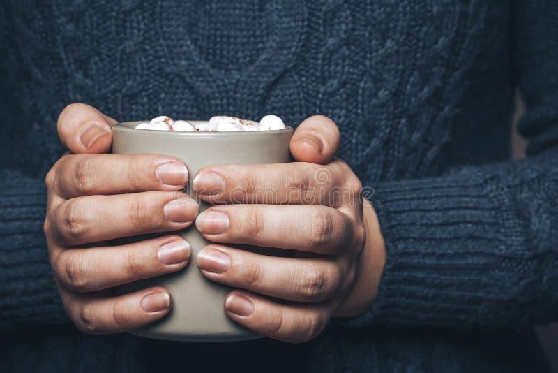 Dziewczyn ręki w pulowerze trzymają filiżankę gorący kakao lub kawa z marshmallow, tonującą obraz stock