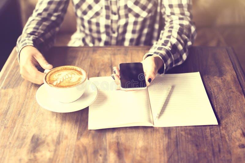 Dziewczyn ręki z telefonem komórkowym, cappuccino i puste miejsce dzienniczkiem z penc, zdjęcia stock