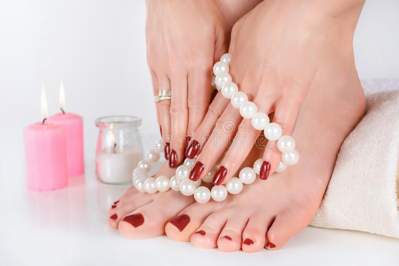 Dziewczyn ręki z zmrokiem i cieki - czerwonego koloru pedicure i manicure fotografia stock