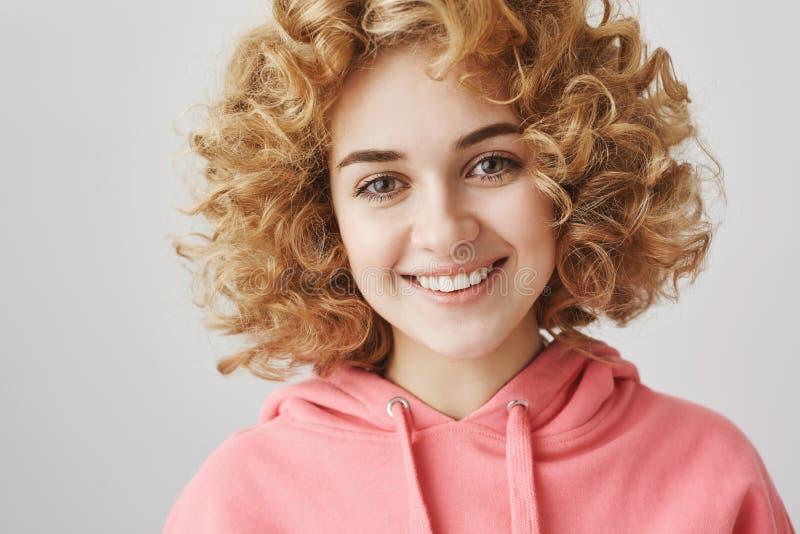 Dziewczyn spojrzenia jak amorek Portret atrakcyjna życzliwa kobieta ono uśmiecha się radośnie z kędzierzawym włosy podczas gdy st zdjęcia stock