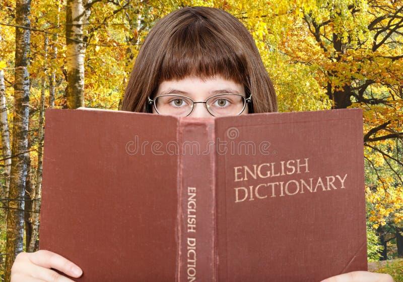 Dziewczyn spojrzenia nad Angielskim słownikiem obraz stock