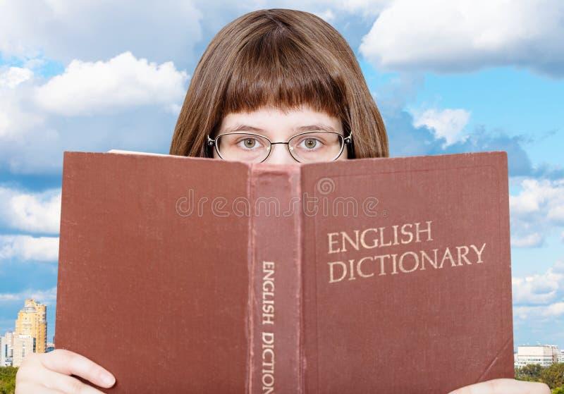 Dziewczyn spojrzenia nad Angielskim słownikiem i bielem chmurnieją fotografia royalty free