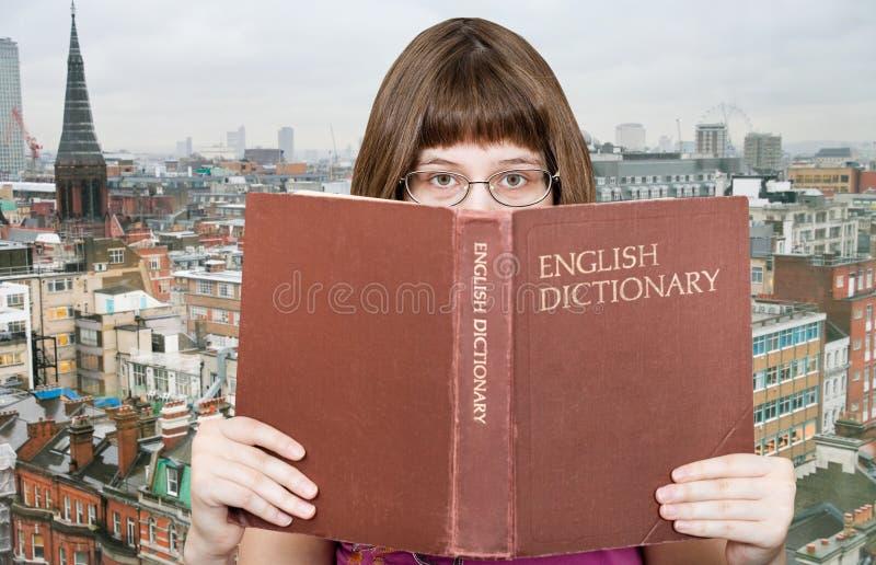 Dziewczyn spojrzenia nad Angielskim słownikiem i linią horyzontu obraz stock
