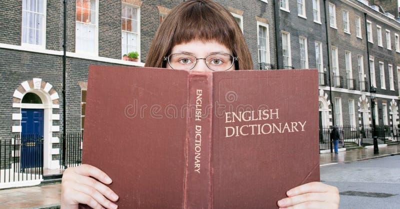 Dziewczyn spojrzenia nad Angielskim słownikiem i ulicą fotografia royalty free