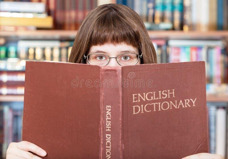 Dziewczyn spojrzenia nad Angielskim słownikiem w bibliotece obraz royalty free