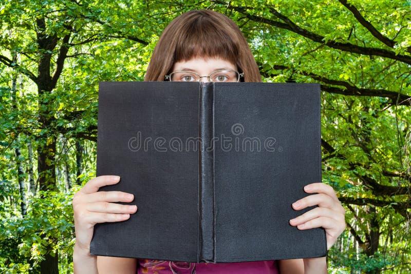 Dziewczyn spojrzenia nad dużymi książkowymi i zielonymi drewnami zdjęcia royalty free