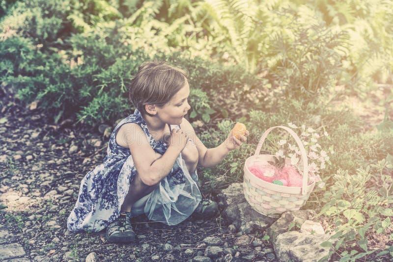 Dziewczyn spojrzenia przy Wielkanocnym jajkiem od jej kosza - Retro zdjęcie stock