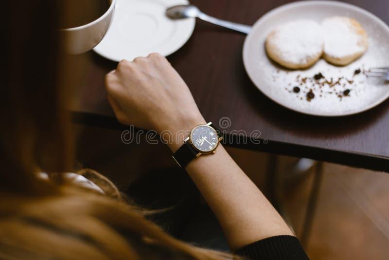 Dziewczyn spojrzenia przy zegarem w kawiarni nad filiżanka kawy czas na zegarze - czas dla śniadania, deser obraz stock