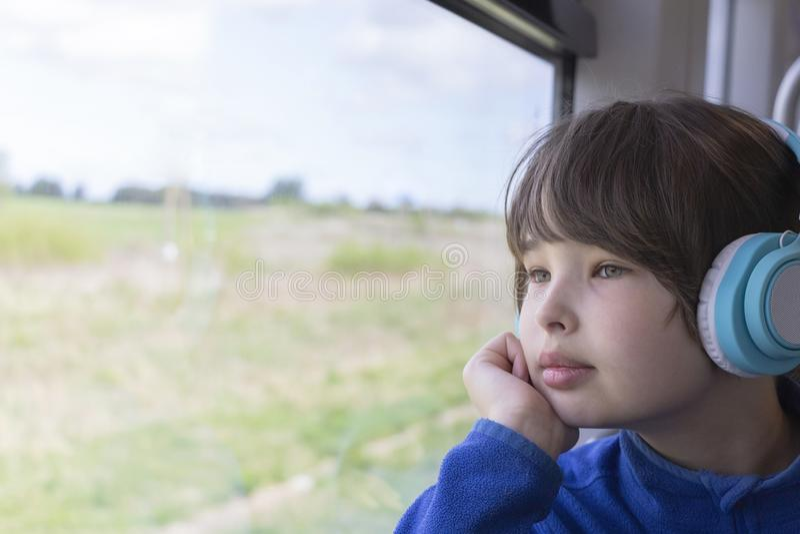 Dziewczyn spojrzenia za okno słuchanie muzyka w hełmofonach i pociąg fotografia royalty free