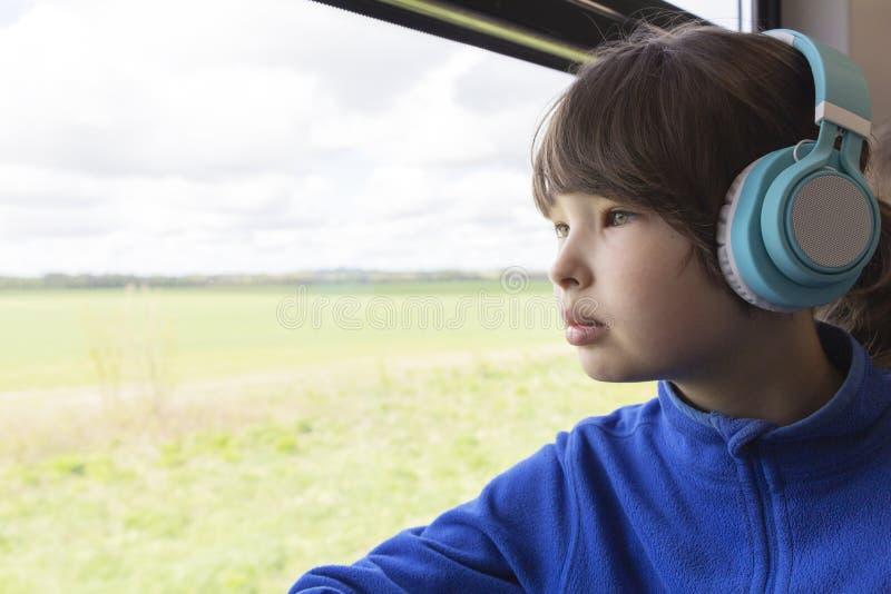 Dziewczyn spojrzenia za okno s?uchanie muzyka w he?mofonach i poci?g fotografia royalty free
