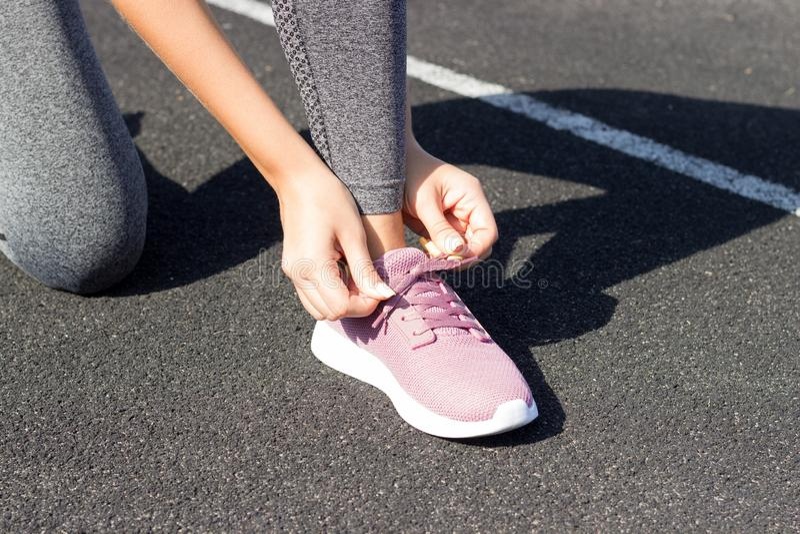 Dziewczyn sznurowania na jego Różowią sneakers dla biegać żadny twarzy zbliżenie Outdoors, światła słonecznego, stadium, sporta i zdjęcia royalty free