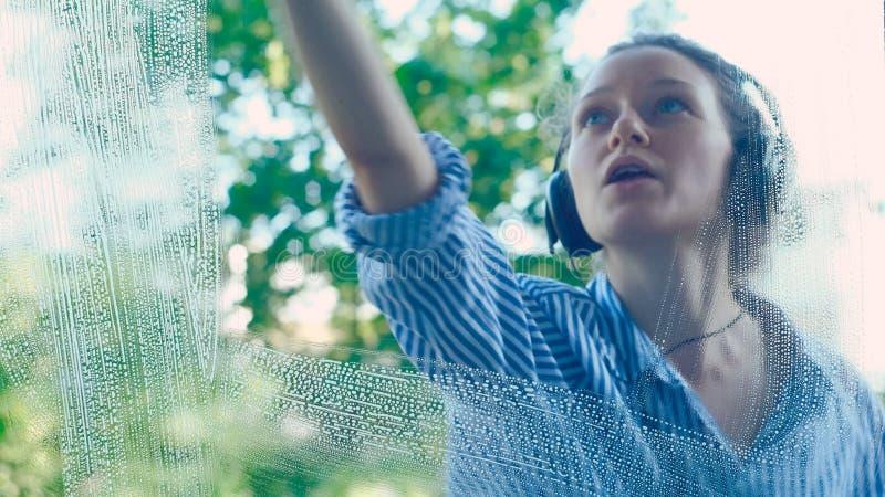 Dziewczyn wytarcia brudzą okno z błękita łachmanem słucha muzyka obrazy stock