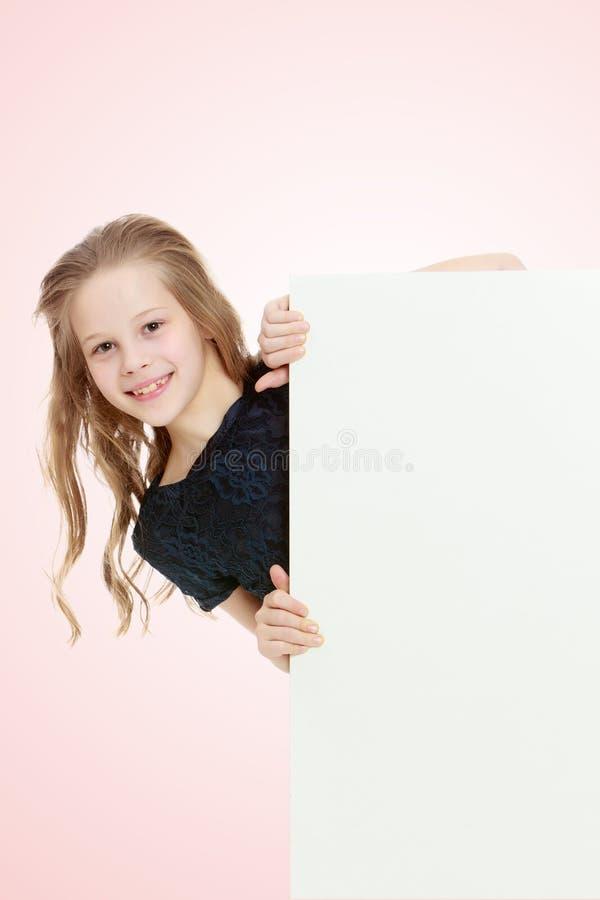 Dziewczyn zerknięcia out od sztandaru za fotografia stock