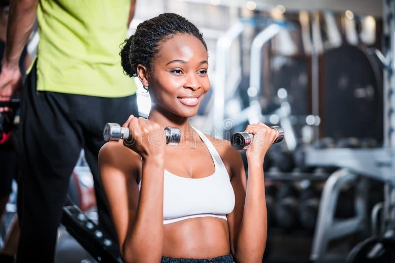 Dziewczyna ćwiczy jej ramię w sprawności fizycznej gym zdjęcie stock