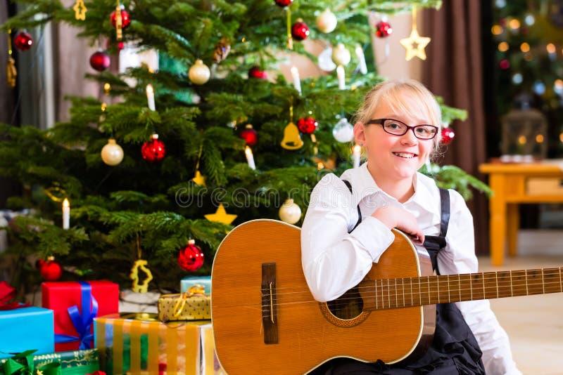 Dziewczyna bawić się gitarę na bożych narodzeniach zdjęcia royalty free