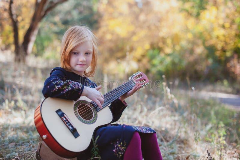 Dziewczyna bawić się gitarę w jesień lesie zdjęcia royalty free