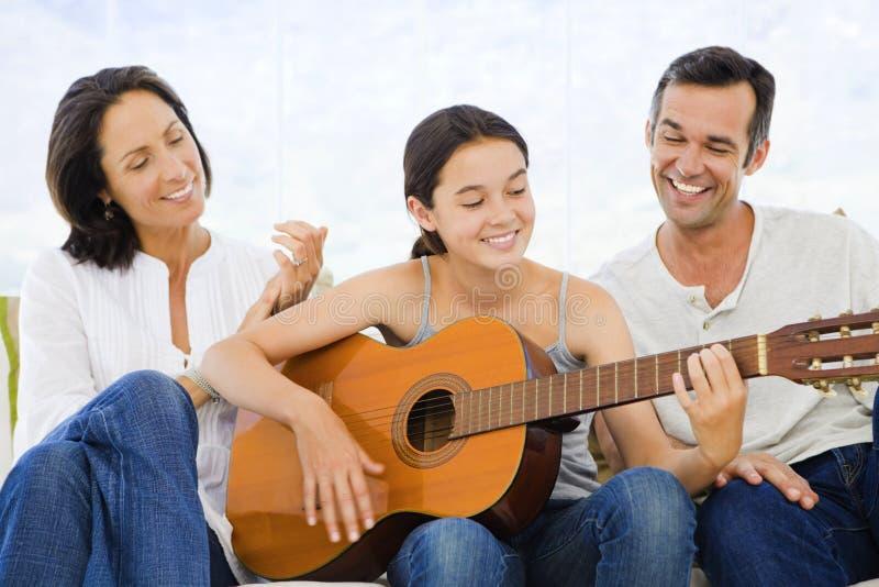 Dziewczyna bawić się gitarę z ona rodzice zdjęcie stock