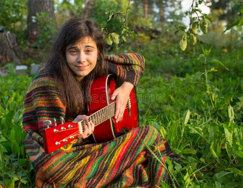 Dziewczyna bawić się gitary obsiadanie na trawie w parku zdjęcia stock