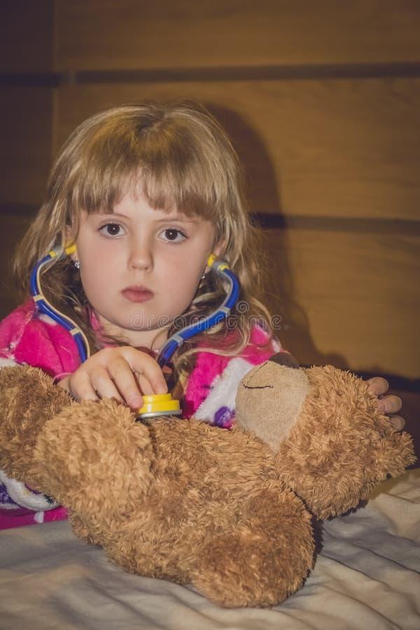 Dziewczyna bawić się lekarkę z misiem fotografia royalty free