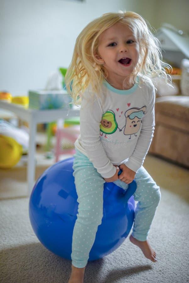 Dziewczyna bawić się na pełen wigoru piłce i śmiać się zdjęcie royalty free