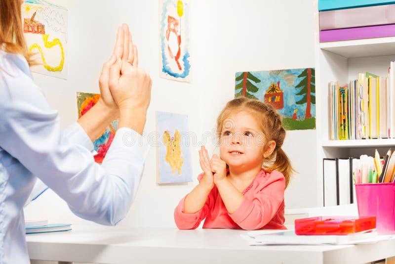 Dziewczyna bawić się palcowe gry z nauczycielem fotografia stock