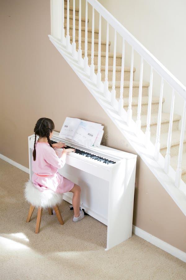 Dziewczyna bawić się pianino w domu obraz stock